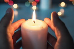 Person holding small lit candle in their hands, representing a loved one's life and meaning