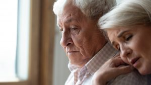 Sad older man and woman, woman laying head on shoulder of man in comfort