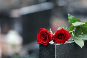 Two red roses laying across top of dark marble grave marker in cemetery