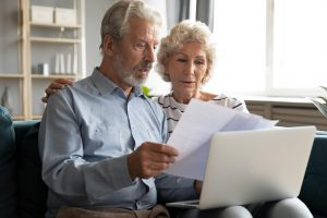 Older husband and wife sitting on couch at home, looking at document and reviewing interment options