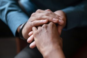 Focus on hands, one person holding another person's hand in a comforting way