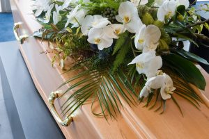 Light wood casket with white lilies and greenery to illustrate traditional burial