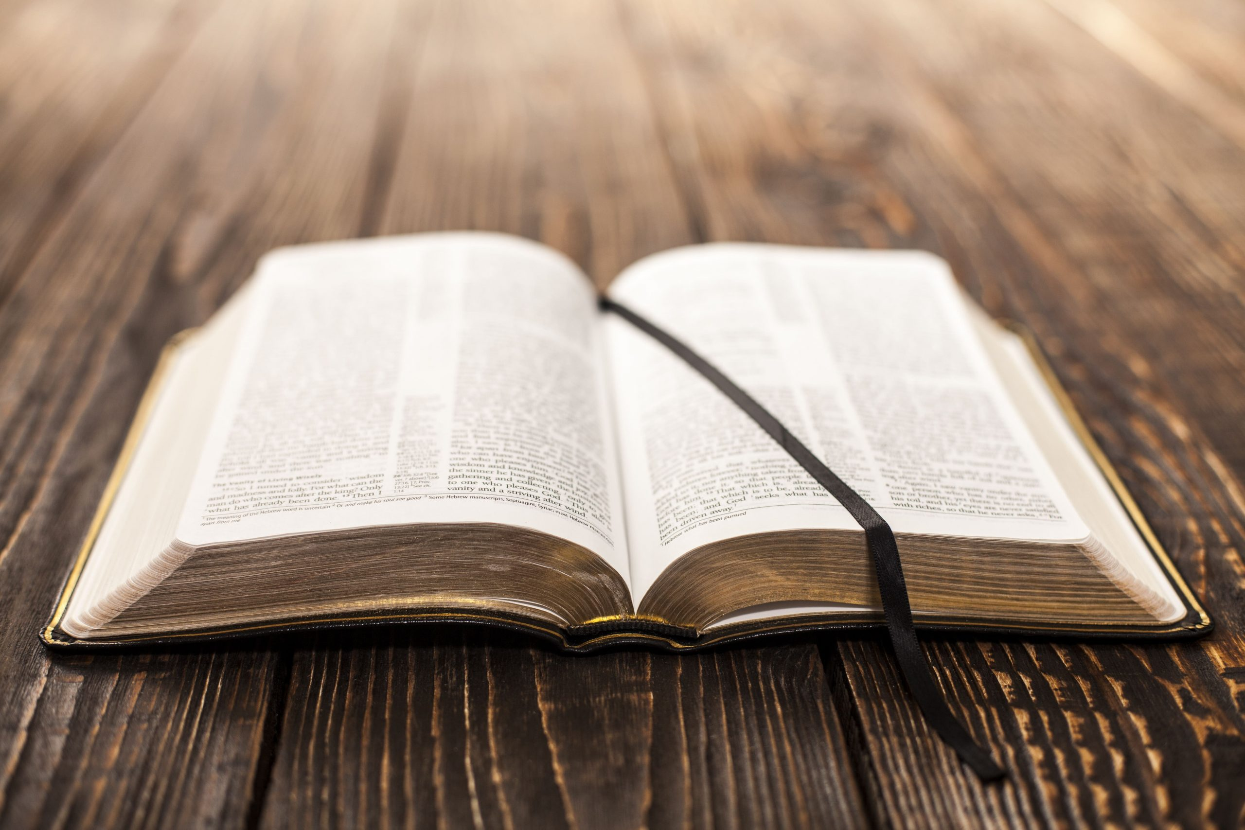 Bible laying open on wooden table