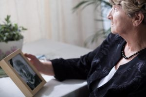 Older woman sitting at table, holding picture of loved one and thinking