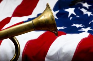 Majority of bugle visible against the backdrop of an American flag