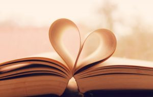 Open book with pages folded together in middle to create a heart