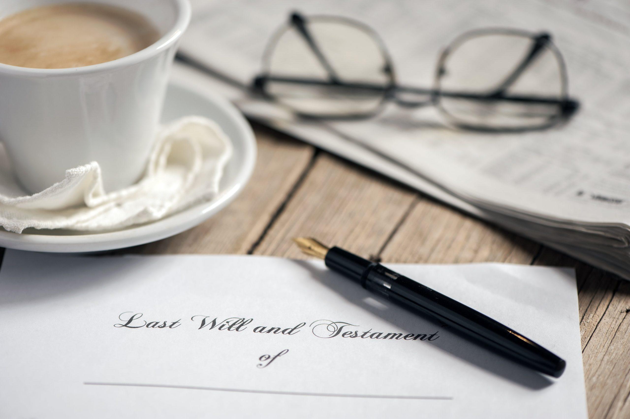 Folded legal will sitting on table near coffee mug, pen, and eyeglasses