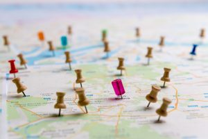 Pushpins tacked into a map, showing locations