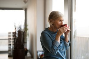 Older woman standing in her home, sipping on a cup of tea, finding a way to move forward and heal