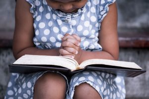 Young girl sitting on steps outside, Bible in lap, hands clasped in prayer