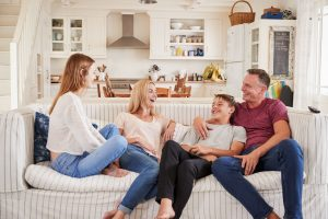 Blended family sitting on couch, enjoying each other's company, mom, dad, teenage son, and teenage daughter present
