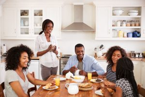 Blended family of 5 sitting at breakfast table, eating a meal together