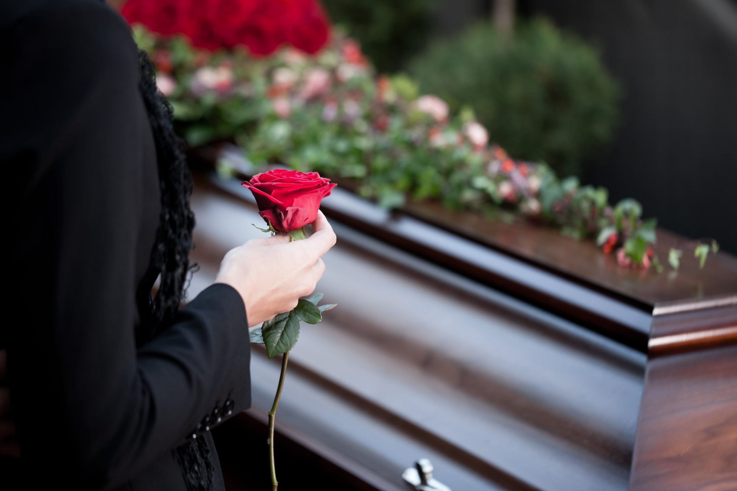 Woman wearing black and holding red rose as she stands beside a dark wood casket covered in flowers