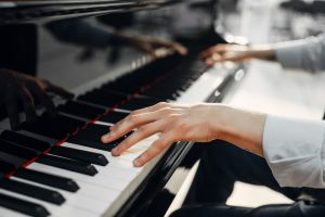 Man playing piano, focus on hands