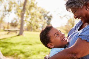 Grandmother hugging grandson, both smiling