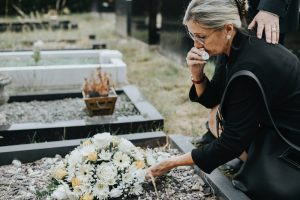 Grieving woman laying flowers on a loved one's grave