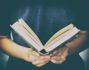 Person wearing dark shirt and holding open book