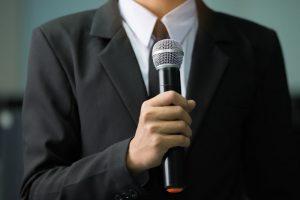 Man in dark suit speaking into microphone