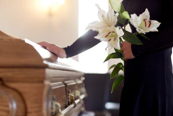 Woman standing next to casket while holding white lilies